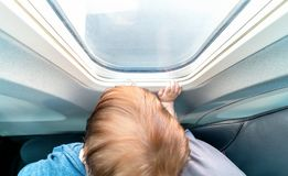 Toddler boy looking out a plane window. Little toddler boy looking out an airplane window while flying Stock Photography