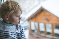 Little toddler boy looking out of the window on winter day with Stock Image