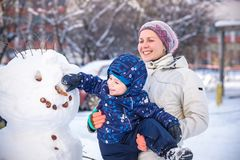 Little toddler boy making snowman outdoors on beautiful winter day royalty free stock images