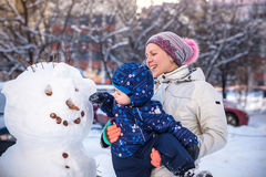 Little toddler boy making snowman outdoors on beautiful winter day Royalty Free Stock Photo