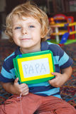 Little toddler boy with painting board writes his first word Stock Photos