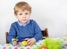 Little toddler boy painting colorful eggs for Easter hunt Royalty Free Stock Image