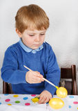 Little toddler boy painting colorful eggs for Easter hunt Stock Image