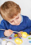 Little toddler boy painting colorful eggs for Easter hunt Stock Photography