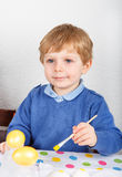 Little toddler boy painting colorful eggs for Easter hunt Stock Images