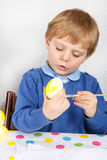 Little toddler boy painting colorful eggs for Easter hunt Royalty Free Stock Photo