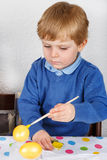 Little toddler boy painting colorful eggs for Easter hunt Royalty Free Stock Images