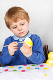 Little toddler boy painting colorful eggs for Easter hunt Stock Photo