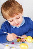 Little toddler boy painting colorful eggs for Easter hunt Royalty Free Stock Photos