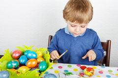 Little toddler boy painting colorful eggs for Easter hunt Royalty Free Stock Photography