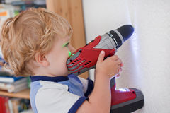 Little toddler boy playing with drill indoor Stock Photo
