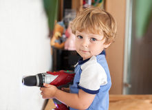 Little toddler boy playing with drill indoor Royalty Free Stock Photos