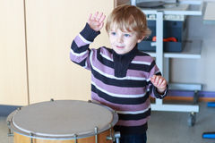 Little toddler boy playing drum at music school. Stock Photo