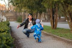 Little toddler boy playing with father in the spring park: boy is running to dad, man is catching him with arms wide open stock photos