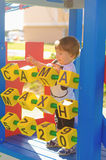 Little toddler boy playing on the playground with cubes. Royalty Free Stock Photo