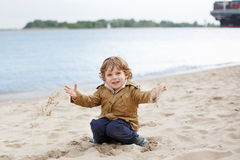 Little toddler boy playing with sand on beach of the river Elbe Royalty Free Stock Photo