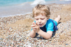 Little toddler boy playing with sand and stones on the beach Stock Photo