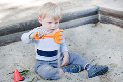 Little toddler boy playing with sand and toy Stock Photo
