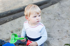 Little toddler boy playing with sand and toy Stock Images