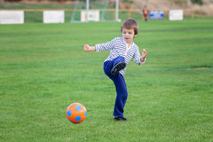 Little toddler boy playing soccer and football, having fun outdo Stock Image