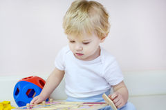 Little toddler boy playing with wooden puzzle toys Stock Images