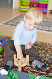 Little toddler boy playing with wooden toys Stock Photos