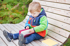Little toddler boy reading book outdoors. Little toddler boy reading book on bench in autumn park Stock Photos
