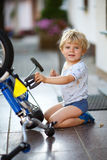 Little toddler boy repairing his first bike Royalty Free Stock Photography