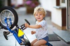 Little toddler boy repairing his first bike Royalty Free Stock Image