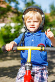 Little toddler boy riding on his bycicle in summer Royalty Free Stock Photo