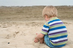 Little toddler boy sitting back on sandy beach Royalty Free Stock Images