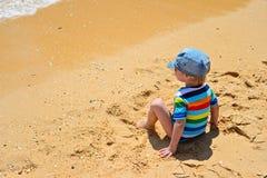 Little toddler boy sitting back on sandy beach Royalty Free Stock Photos