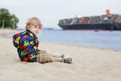 Little toddler boy sitting on sand beach and looking on containe. R ship, outdoors Royalty Free Stock Photography