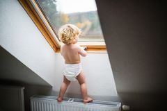 Toddler boy in a dangerous situation at home. Little toddler boy standing on a radiator, opening a window. Domestic accident. Dangerous situation at home. Rear Royalty Free Stock Image