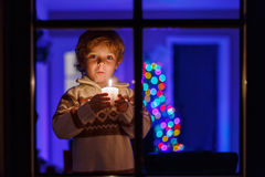 Little toddler boy standing by window at Christmas time and hold Stock Photo