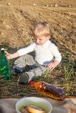 Little toddler boy of two years making picnic on golden hay fiel Royalty Free Stock Image