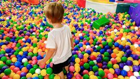 Little toddler boy walking and climbing over lots of colorful plastic ball on the playground at shopping mall. Little boy walking and climbing over lots of royalty free stock photos