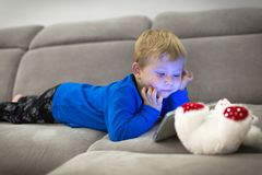 Little toddler boy watch cartoons. On the tablet royalty free stock photo
