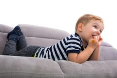 Boy watching TV on the coach. Little toddler boy watching TV on the coach Stock Photo