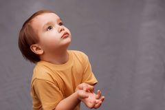 Little toddler boy in yellow shirt standing and looking up asking for something. The kid is holding hands raised to chest like he stock photos