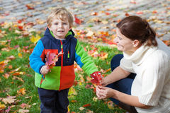 Little toddler boy and young mother in the autumn park Royalty Free Stock Photo