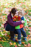 Little toddler boy and young mother in the autumn park Stock Images