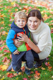 Little toddler boy and young mother in the autumn park Stock Photos