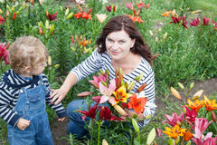 Little toddler boy and young woman on lily field in summer Royalty Free Stock Photography