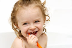 Little toddler brushing teeth in the bath Stock Photo