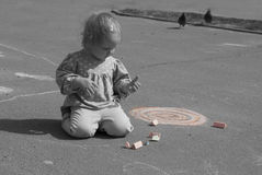 Little toddler with a chalk outdoors Stock Images