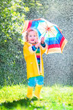 Little toddler with colorful umbrella playing in rain Stock Image