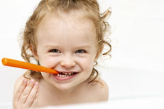Little toddler devil cleaning teeth in the bath Royalty Free Stock Photo