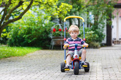 Little toddler driving tricycle or bicycle in home garden Royalty Free Stock Photo