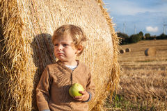 Little toddler eating apple with a big hay bale on field Royalty Free Stock Photos